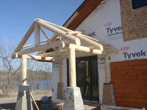Store entrance log archway under construction | trusses